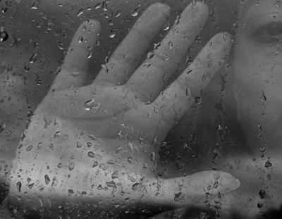 Hand on glass wet because of the rain